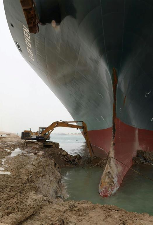 An excavator is used to try to release the MV Ever Given, which has been stuck in the Suez Canal since Tuesday