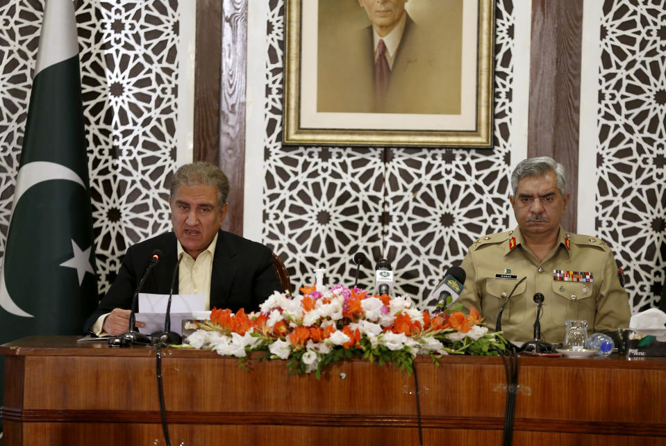Pakistan's Foreign Minister Shah Mahmood Qureshi, left, briefs to media while military spokesman Maj. Gen. Babar Iftikhar listens during a joint press conference regarding on going tension between Pakistan and India, in Islamabad, Pakistan, Saturday, Nov. 14, 2020. Pakistani and Indian troops clashed in disputed Kashmir, causing casualties and wounding more than 30 others on both sides, officials said. The fighting came amid increasing tension between the South Asian neighbors. (AP Photo/Anjum Naveed)