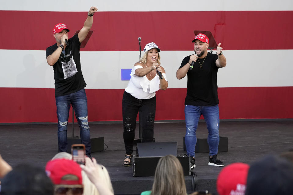 """FILE- In this Tuesday, Oct. 27, 2020 file photo, members of the Cuban musical group Los 3 de La Habana, German Pinelli, left, Ana Paez, center, and Tirso Luis, right, sing during a """"Make America Great Again!"""" event with Ivanka Trump at Bayfront Park Amphitheater, in Miami. Florida's Cuban American voters remain a bright spot in Trump's effort to retain his winning coalition from 2016. Polls show his strong support from these key voters may even be growing to include the younger Cuban Americans that Democrats once considered their best hope of breaking the GOP's hold. The musicians say Trump's economic and foreign policies have been his main achievements. (AP Photo/Wilfredo Lee, File)"""