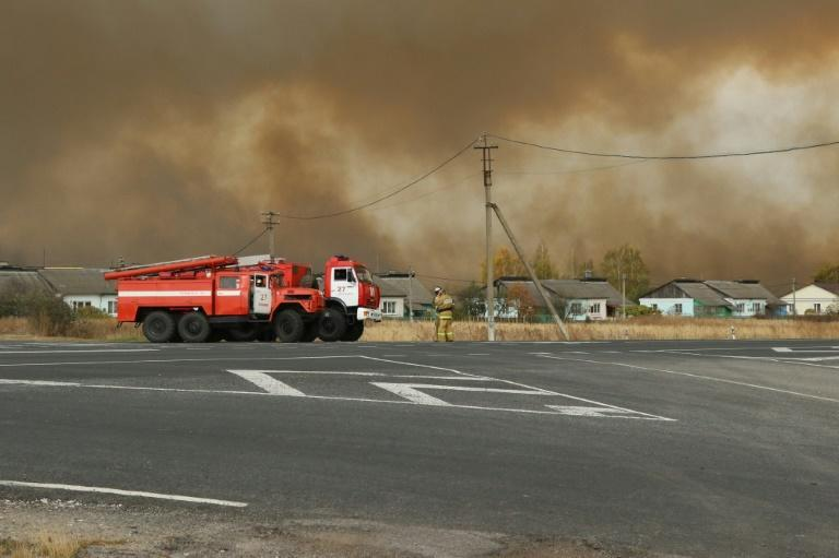 Smoke rises from a fire at a munitions depot as fire engines are seen on a road in the Ryazan region on October 7, 2020