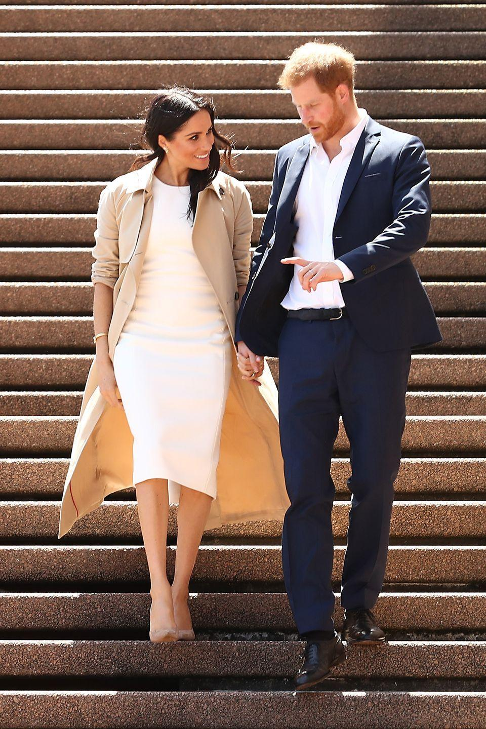 """<p>Stepping out in Sydney, the mother-to-be wore a pair of stunning gold butterfly earrings to complement her form-fitting ivory shift dress (appropriately dubbed the <a href=""""https://karengee.com/blessed-dress.html"""" rel=""""nofollow noopener"""" target=""""_blank"""" data-ylk=""""slk:'Blessed' dress"""" class=""""link rapid-noclick-resp"""">'Blessed' dress</a>) by Sydney-based designer Karen Gee and nude-coloured suede <a href=""""https://www.stuartweitzman.com/products/legend/"""" rel=""""nofollow noopener"""" target=""""_blank"""" data-ylk=""""slk:Stuart Weitzman 'Legend' pumps"""" class=""""link rapid-noclick-resp"""">Stuart Weitzman 'Legend' pumps</a>.</p>"""