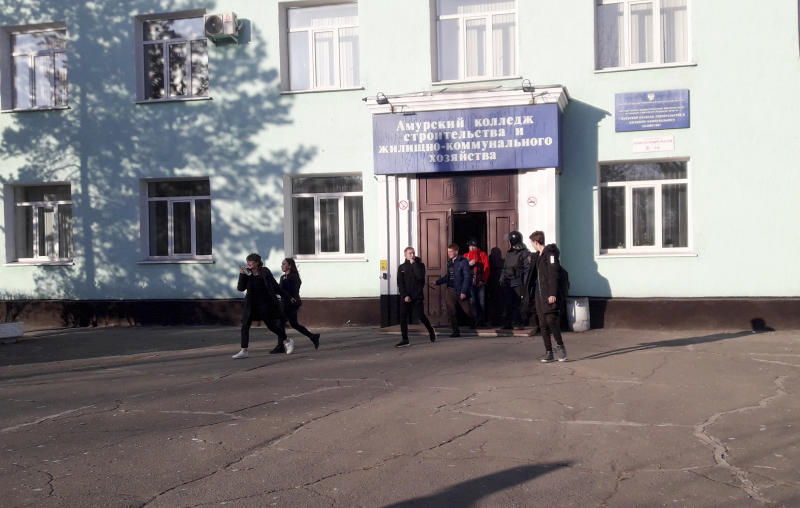 In this photo provided by Vera Zaderko, students leave a college after a shooting in Blagoveshchensk, Russia, Thursday, Nov. 14, 2019. Russia's state Investigative Committee said the 19-year-old college student in Blagoveshchensk near the border with China brought a hunting rifle to class Thursday and opened fire on students, shooting one dead and severely injuring three more. It wasn't immediately clear what prompted the attack. The attacker shot himself soon after the police arrived. (Vera Kulikova via AP)