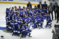 The Tampa Bay Lightning pose at center ice after defeating the Montreal Canadiens in Game 5 of the NHL hockey Stanley Cup finals, Wednesday, July 7, 2021, in Tampa, Fla. (AP Photo/Gerry Broome)