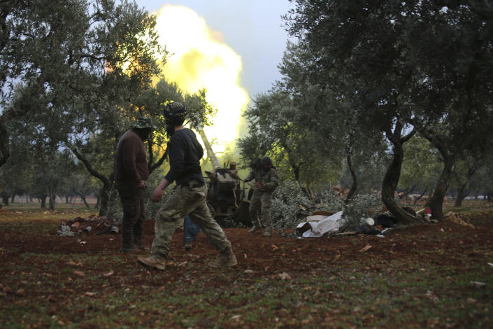 Syrian rebel fighter fire a howitzer toward the government positions near the village of Nerab, in Idlib province, Thursday, Feb. 6, 2020. Turkey sent more reinforcements into northwestern Syria on Thursday, setting up new positions in an attempt to stop a Syrian government offensive on the last rebel stronghold in the war-torn country, state media and opposition activists said. (AP Photo/Ghaith Alsayed)