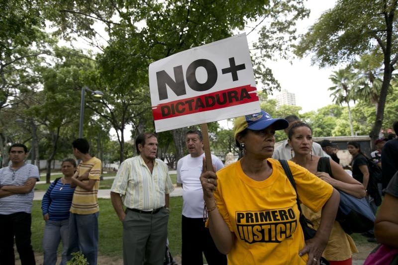 "A woman holds up a sign that reads in Spanish read ""No more dictatorship"" during a protest outside of Venezuela's General Prosecutor's office in Caracas, Venezuela, Friday, March 31, 2017. Security forces violently repressed small protests that broke out in Venezuela's capital Friday after the government-stacked Supreme Court gutted congress of its last vestiges of power, drawing widespread condemnation from foreign governments. (AP Photo/Ariana Cubillos)"