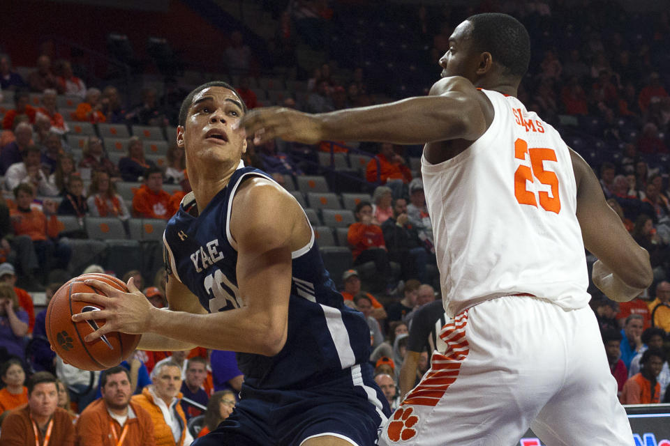Dec 22, 2019; Clemson, South Carolina, USA; Yale Bulldogs forward Paul Atkinson (20) drives to the basket while being defended by Clemson Tigers forward Aamir Simms (25) during the first half of the game at Littlejohn Coliseum.