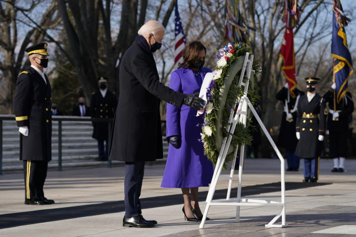 FILE - In this Wednesday, Jan. 20, 2021 file photo, President Joe Biden and Vice President Kamala Harris participate in a wreath laying ceremony at the Tomb of the Unknown Soldier at Arlington National Cemetery in Arlington, Va. On Friday, Feb. 19, 2021, The Associated Press reported on a video circulating online incorrectly asserting that footage shows certain aspects of the wreath-laying ceremony for President Joe Biden at the Tomb of the Unknown Soldier on Jan. 20 were different from past presidents' ceremonies, proving Biden's inauguration was fake. Differences between Biden's ceremony at the Arlington National Cemetery and other presidential wreath-laying ceremonies in the past can be attributed to cold weather and coronavirus precautions, according to a spokesperson for the U.S. Army Military District of Washington. (AP Photo/Evan Vucci)