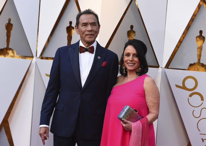 FILE - This March 4, 2018 file photo shows Wes Studi, left, and Maura Dhu at the Oscars in Los Angeles. Studi will become the first Native American actor to receive an Oscar Sunday night at the Governors Awards. (Photo by Jordan Strauss/Invision/AP, File)