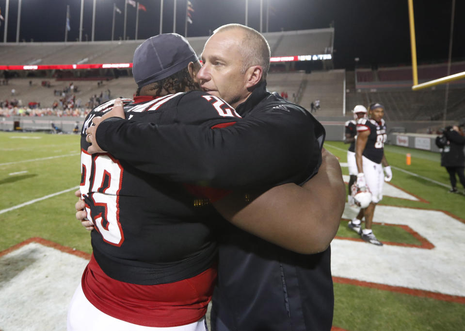 North Carolina State coach Dave Doeren hugs defensive tackle Alim McNeill (29) after the team's 23-13 victory over Georgia Tech in an NCAA college football game in Raleigh, N.C., Saturday, Dec. 5, 2020. (Ethan Hyman/The News & Observer via AP, Pool)