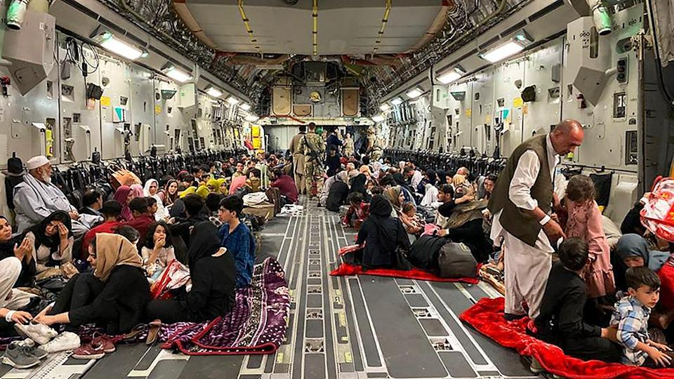 Afghans sit inside a US military aircraft waiting to leave Afghanistan, at the military airport in Kabul - 19 August 2021