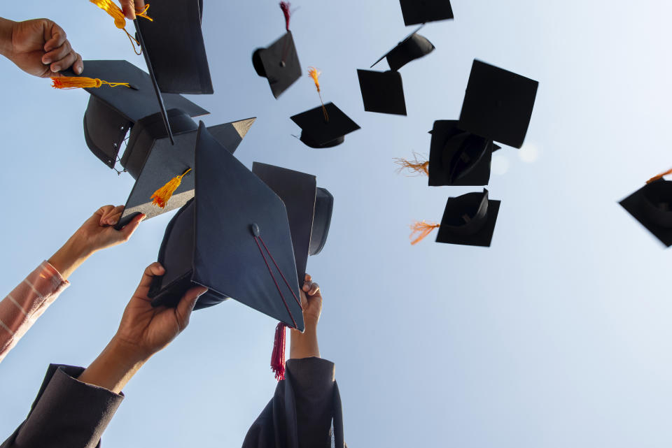 Cropped Hands Of People Throwing Mortarboards Against Clear Sky