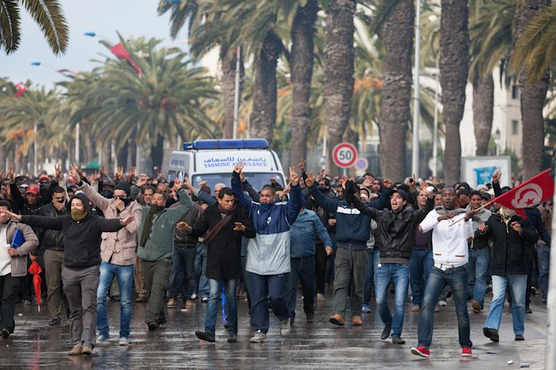 Protesters gather at the ambulance carrying the body of opposition leader Chokri Belaid in Tunis, Wednesday, Feb. 6, 2013. The Tunisian opposition leader critical of the Islamist-led government and violence by radical Muslims was shot to death Wednesday, the first political assassination in post-revolutionary Tunisia. The killing is likely to heighten tensions in the North African nation whose path from dictatorship to democracy so far has been seen as a model for the Arab world. (AP Photo/Amine Landoulsi)