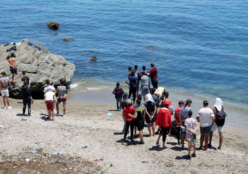 FILE PHOTO: Migrants stand on the beach in Fnideq, close to the Spanish enclave Ceuta