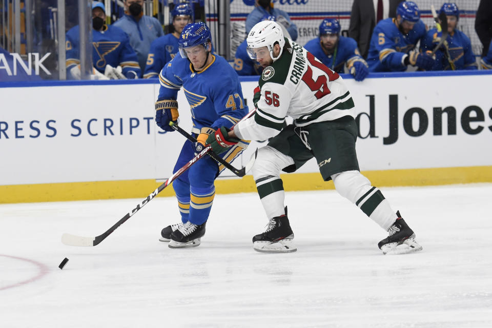St. Louis Blues' Torey Krug (47) and Minnesota Wild's Joseph Cramarossa (56) battle for the puck during the third period of an NHL hockey game on Saturday, April 10, 2021, in St. Louis. (AP Photo/Joe Puetz)