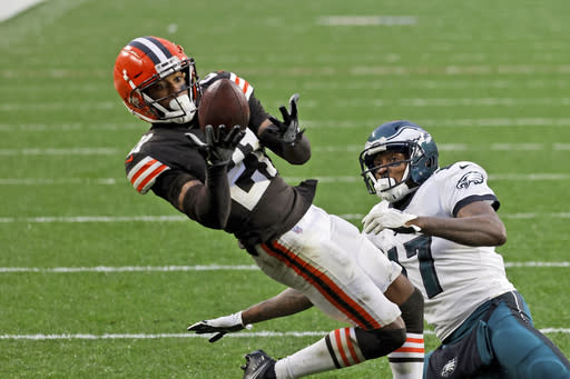 FILE - In this Sunday, Nov. 22, 2020, file photo, Cleveland Browns cornerback Denzel Ward (21) intercepts a pass intended for Philadelphia Eagles wide receiver Alshon Jeffery (17) during an NFL football game in Cleveland. The Browns may have their best cornerback in the lineup on Sunday for the first of two straight weekend trips to New York. Cornerback Denzel Ward, who playing at a Pro Bowl level when he got hurt, returned to practice Wednesday after missing three games with a strained calf. (AP Photo/Kirk Irwin, File)