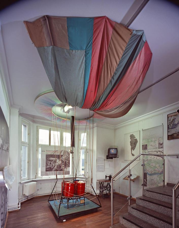 """<p>One of the most famous escapes involved a <a href=""""https://www.theguardian.com/world/2018/oct/07/east-germany-balloon-escape-film-revives-german-identity-debate"""" rel=""""nofollow noopener"""" target=""""_blank"""" data-ylk=""""slk:hot air balloon"""" class=""""link rapid-noclick-resp"""">hot air balloon</a> put together by mechanic Peter Strelzyk and bricklayer Günter Wetzel. The balloon was carefully engineered to provide enough lift to carry the two men and their families. The burner was a modified propane tank; the envelope was a stitched-together patchwork of synthetic taffeta in different patterns. </p><p>This was bought at several different shops to avoid arousing suspicion. On September 16th, 1979, the two men, with their wives and four children, ascended to a height of eight thousand feet—high enough to avoid East German searchlights—and made a terrifying 25-minute trip. The balloon fabric tore towards the end and Wetzel broke his leg on landing, but all made it safely to the West.</p>"""