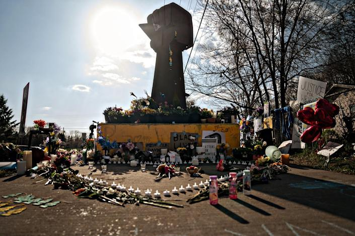 Candles, flowers, signs and other items sit on the ground before a statue of a raised fist