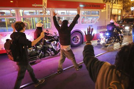 Protesters hold their hands up while marching down Market Street during a demonstration against the grand jury decision in the Ferguson, Missouri shooting of Michael Brown in San Francisco, California November 28, 2014.   REUTERS/Elijah Nouvelage