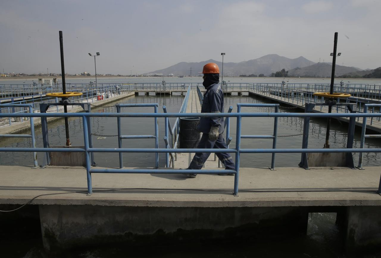 CORRECTS DAY OFTHE WEEK - In this Thursday, Aug. 17, 2017 photo, a worker walks inside SEDAPAL, the state water supply company, in Lima, Peru. Water is collected from lagoons, dams, rivers and underground wells, and brought to Peru's desert capital. In the richest parts of Lima residents use 447 liters a day, nearly five times what is recommended by the World Health Organization. (AP Photo/Martin Mejia)