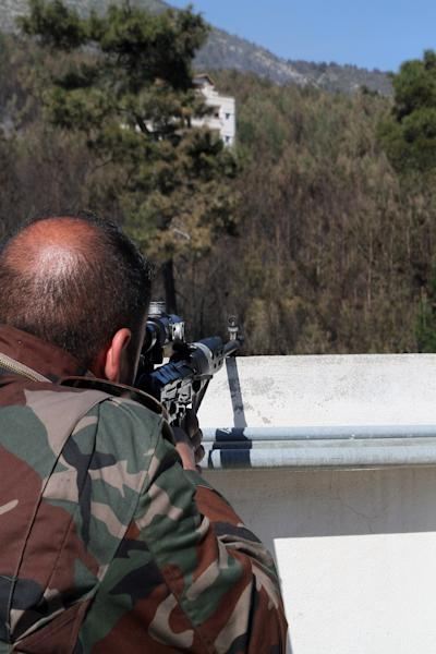 In this photo taken Thursday, March 27, 2014, a Syrian government soldier takes position during clashes with rebels in Misherfeh town in the province of Latakia, Syria. Syrian forces on Thursday bombarded rebel positions with artillery and warplanes in the Mediterranean coastal province of Latakia, trying to push back opposition fighters who over the past week made rare territorial gains in President Bashar Assad's ancestral heartland. (AP Photo)