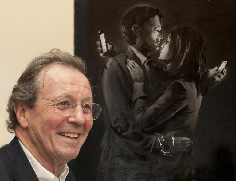 George Ferguson, Mayor of Bristol, poses next to an artwork named 'Mobile Lovers', by British artist Banksy, as it is unveiled at the City Museum in Bristol, southwest England on April 17, 2014
