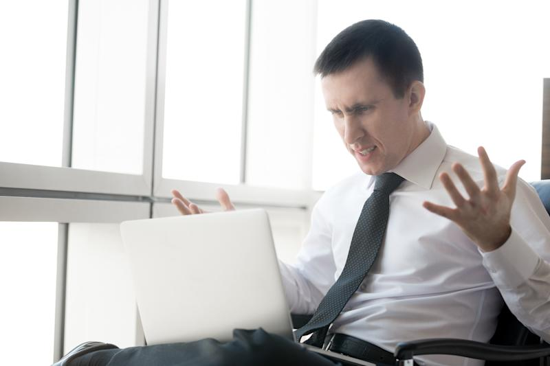 A visibly frustrated businessman throwing his hands up in the air while reading information on his laptop.