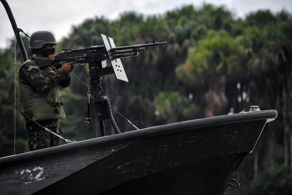 A member of the Brazilian Armed Forces taked part in a military exercise as part of the Agata operation, on the Oiapoque River in Oiapoque, Amapa state, Brazil, on the border with French Guiana, on October 31, 2020. - The Agata operation carried out by the Armed Forces, Federal Police, Federal Revenue and the Brazilian Institute for the Environment and Renewable Natural Resources (IBAMA), consists in combating drug and arms trafficking, smuggling, illegal mining and fishing, boat theft and irregular transportation of wood and fuel, in the states of Para and Amapa. (Photo by NELSON ALMEIDA / AFP) (Photo by NELSON ALMEIDA/AFP via Getty Images)