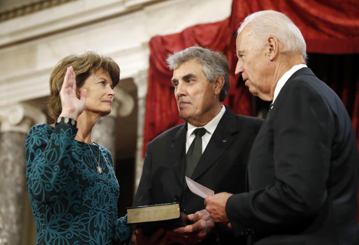 FILE - In this Jan. 3, 2017, file photo, Vice President Joe Biden, right, after administers the Senate oath of office to Sen. Lisa Murkowski, R-Alaska, as her husband Verne Martell holds a Bible, during a mock swearing in ceremony in the Old Senate Chamber on Capitol Hill in Washington as the 115th Congress begins. The oath, which normally doesn't attract much attention, has become a common subject in the final days of the Trump presidency, being invoked by members of both parties as they met Wednesday, Jan. 6, 2021 to affirm Biden's win and a pro-Trump mob stormed the U.S. Capitol. Murkowski vowed to honor the oath she took and affirm the results of the presidential election while urging colleagues to do the same. (AP Photo/Alex Brandon, File)
