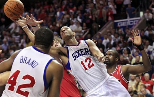 Philadelphia 76ers' Evan Turner (12) takes a shot past Chicago Bulls' Luol Deng, right, late in the fourth quarter of Game 3 in an NBA basketball first-round playoff series in Philadelphia, Friday, May 4, 2012. The 76ers won 79-74. (AP Photo/Mel Evans)
