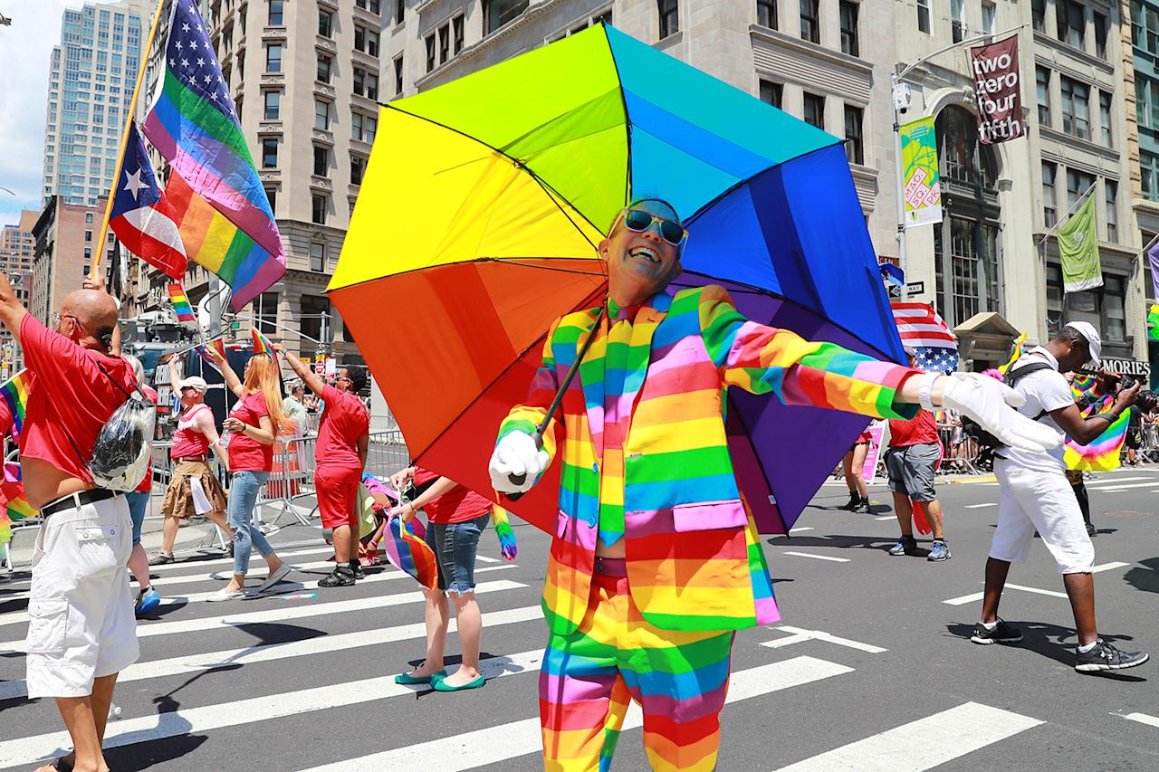 <p>A marcher carrying an umbrella and dressed as a rainbow gestures for the camera during the N.Y.C. Pride Parade in New York on June 25, 2017. (Photo: Gordon Donovan/Yahoo News) </p>