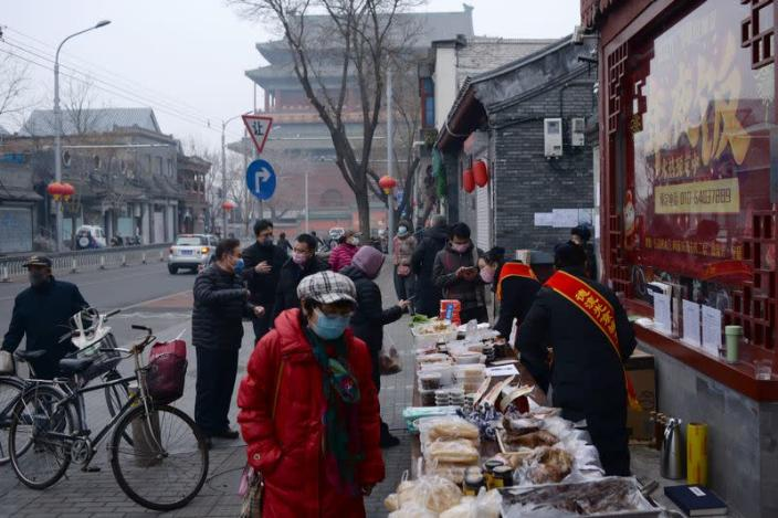 People wearing face masks buy food from a stall set up by a restaurant outside its outlet in Beijing