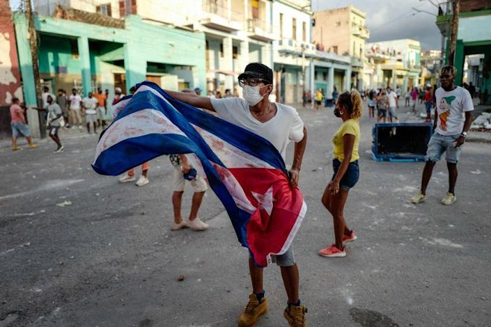 A man waves a Cuban flag during a demonstration against the government of Cuban President Miguel Diaz-Canel in Havana, on July 11, 2021. - Thousands of Cubans took part in rare protests Sunday against the communist government, marching through a town chanting