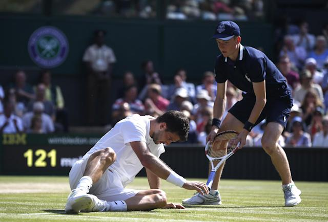 Grigor Dimitrov of Bulgaria has his racquet handed to him by a ball boy after he fell as he played against Novak Djokovic of Serbia during their men's singles semifinal match at the All England Lawn Tennis Championships in Wimbledon, London, Friday, July 4, 2014. (AP Photo/Pavel Golovkin)