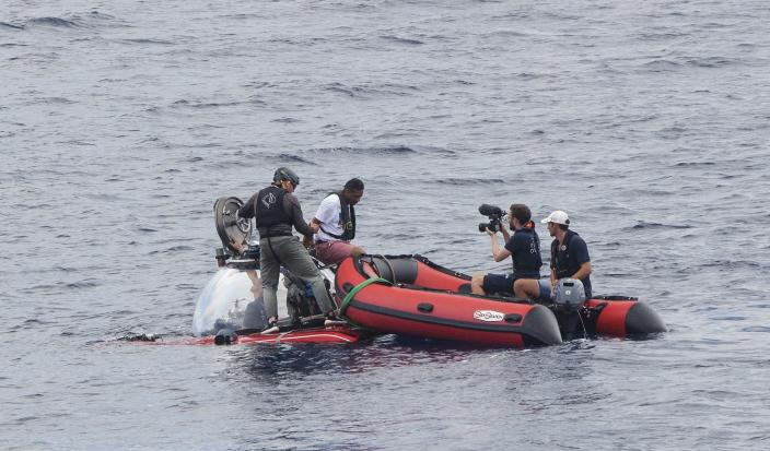 "Seychelles President Danny Faure disembarks from a submersible, off the coast of Seychelles on Sunday April 14, 2019. In a striking speech delivered from deep below the ocean's surface, the Seychelles president on Sunday made a global plea for stronger protection of the ""beating blue heart of our planet."" President Danny Faure's call for action, the first-ever live speech from an underwater submersible, came from one of the many island nations threatened by global warming.(AP Photo/Steve Barker)"