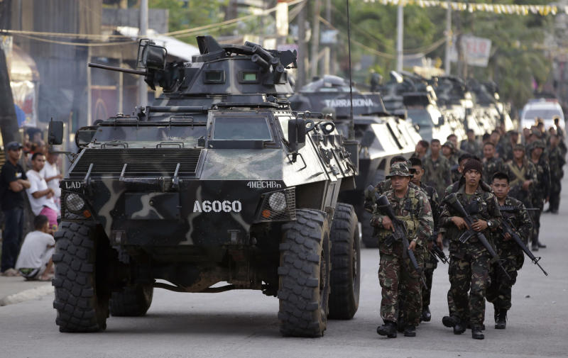 Government troops take their positions as about 200 Muslim rebels, enraged by a broken peace deal with the Philippine government, held scores of hostages as human shields Tuesday Sept. 10, 2013 in a standoff with government forces for the second day with no solution in sight at the southern port city of Zamboanga, in southern Philippines. More battle-ready troops and police were flown to the southern port city of Zamboanga in a bid to end the crisis. The troops have surrounded the Moro National Liberation Front guerrillas with their hostages in four coastal villages since the crisis erupted Monday. (AP Photo/Bullit Marquez)