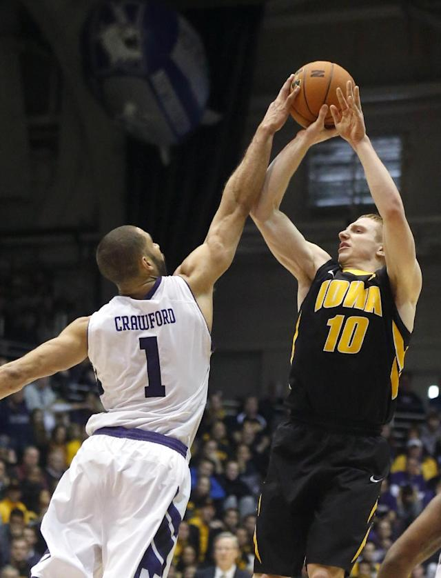 Northwestern guard Drew Crawford (1) blocks a shot by Iowa guard Mike Gesell (10) during the first half of an NCAA college basketball game Saturday, Jan. 25, 2014, in Evanston, Ill. (AP Photo/Charles Rex Arbogast)