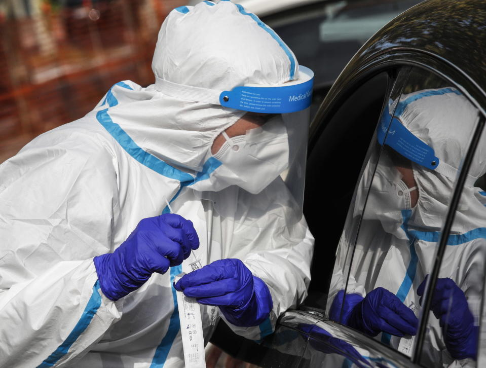 A medical worker performs a coronavirus test on a person in a car in Italy. Source: EPA