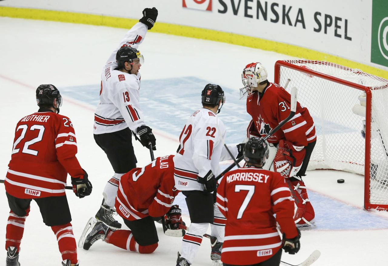 Switzerland's Julian Schmutz (13) celebrates a goal on Canada's goalie Zachary Fucale (R) scored by teammate Nico Dunner (22) during the second period of their IIHF World Junior Championship ice hockey game in Malmo, Sweden, January 2, 2014. REUTERS/Alexander Demianchuk (SWEDEN - Tags: SPORT ICE HOCKEY)