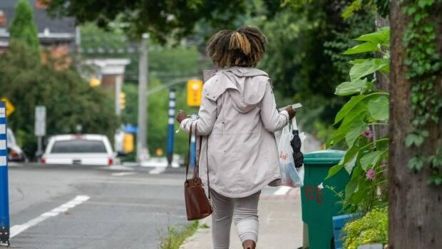 A woman walks down an Ottawa sidewalk carrying a purse, shopping bag and umbrella in late July. (Francis Ferland/CBC - image credit)