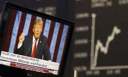 A TV screen showing U.S. President-elect Trump is pictured in front of the German share price index DAX board in Frankfurt