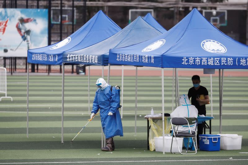 A man in personal protection gear sprays disinfectant at a testing site at the Guangan Sport Center after an unexpected spike of cases of the coronavirus disease (COVID-19) in Beijing