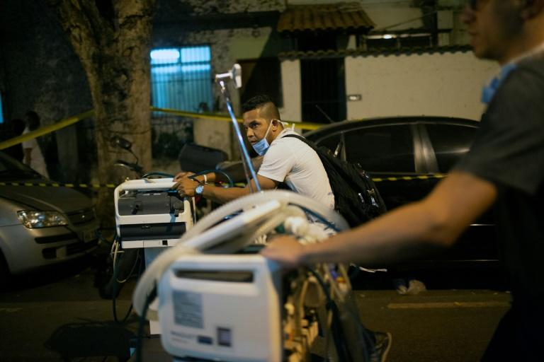 Medical workers carry equipment to ambulances transferring patients out of the Badim hospital in Rio after a fire broke out