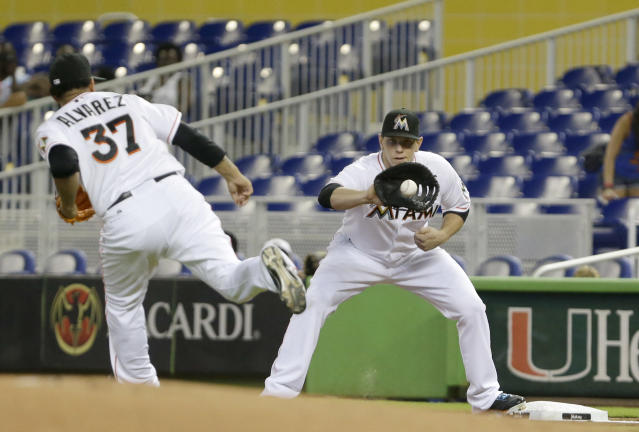 Miami Marlins starting pitcher Henderson Alvarez (37) throws to first baseman Logan Morrison to put out New York Mets' Eric Young during the first inning of a baseball game, Wednesday, July 31, 2013 in Miami. (AP Photo/Wilfredo Lee)