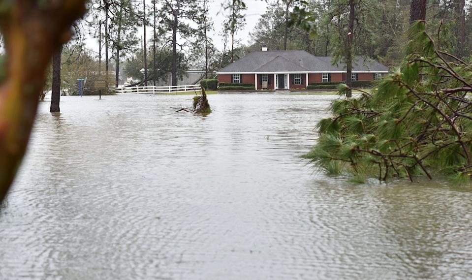A house at the corner of Alabama State Route 59 and Municipal Park Drive, Loxley, Ala., is overtaken by floodwater.