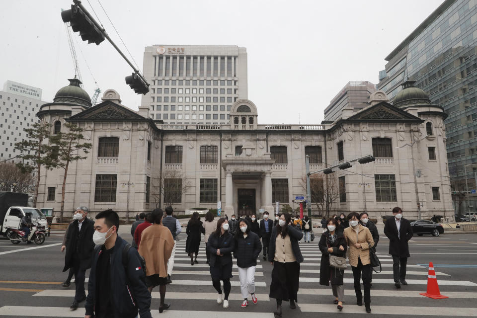 People wearing face masks walk by the headquarters of the Bank of Korea in Seoul, South Korea, Thursday, March 4, 2021. South Korea's central bank says the country's economy shrank for the first time in 22 years in 2020 as the coronavirus pandemic destroyed service industry jobs and depressed consumer spending. (AP Photo/Ahn Young-joon)