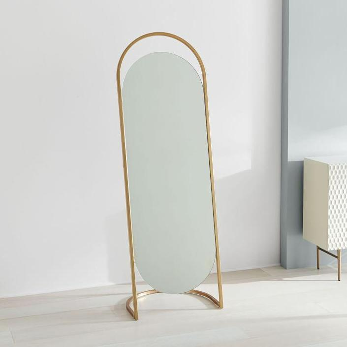 """This freestanding floor mirror incorporates a bit of negative space both at the top and bottom of its oblong shape and is slightly tilted up so you can snap your outfits from the most flattering angles. The smooth gold frame is elegant, while the unorthodox shape adds a little personality. $499, West Elm. <a href=""""https://www.westelm.com/products/folded-ellipse-standing-mirror-h3369/"""" rel=""""nofollow noopener"""" target=""""_blank"""" data-ylk=""""slk:Get it now!"""" class=""""link rapid-noclick-resp"""">Get it now!</a>"""