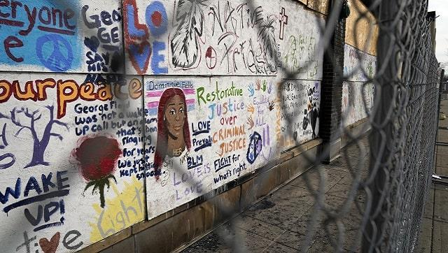 Messages are painted on the side of a building March 22, 2021, in Minneapolis.