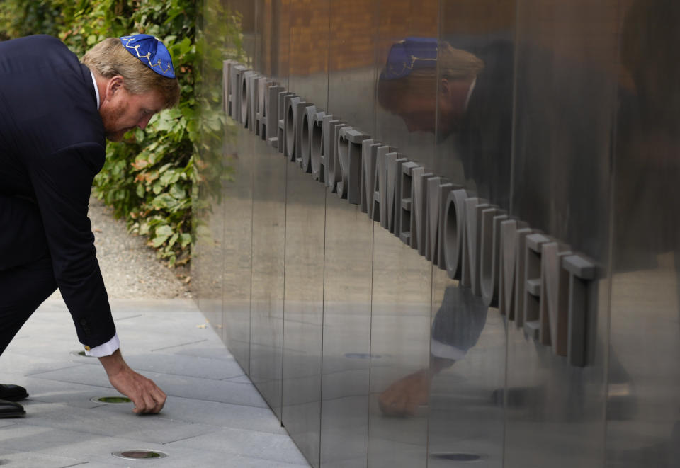 """King Willem-Alexander puts a stone in an act of remembrance when unveiling a new monument in the heart of Amsterdam's historic Jewish Quarter on Sunday, Sept. 19, 2021, honoring the 102,000 Dutch victims of the Holocaust. Designed by Polish-Jewish architect Daniel Libeskind, the memorial is made up of walls shaped to form four Hebrew letters spelling out a word that translates as """"In Memory Of."""" The walls are built using bricks each of which is inscribed with the name of one of the 102,000 Jews, Roma and Sinti who were murdered in Nazi concentration camps during World War II or who died on their way to the camps. (AP Photo/Peter Dejong)"""