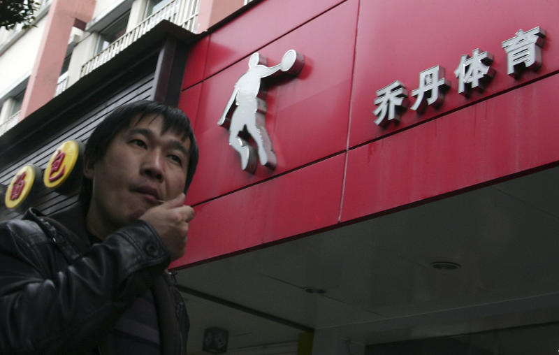 "In this March 5, 2012 photo, a man walks past a shop of ""Qiaodan"" in Shanghai, China.  ""Qiaodan,"" pronounced ""CHEEOW-dan,"" is the moniker former NBA Michael Jordan has been known by in China since he gained widespread popularity in the mid-1980s. Jordan objected to the company using his name, images associated with his own brand including his old jersey number ""23.""  (AP Photo)"