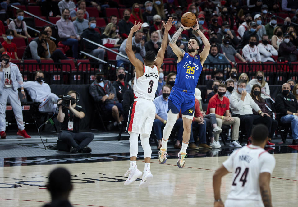 Denver Nuggets guard Austin Rivers shoots a 3-point basket over Portland Trail Blazers guard CJ McCollum during the first half of Game 3 of an NBA basketball first-round playoff series Thursday, May 27, 2021, in Portland, Ore. (AP Photo/Craig Mitchelldyer)